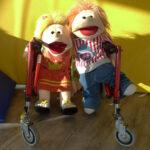 Heilpädagogische Spieltherapie mit Folkmanis Handpuppen und Unterstützung bei der Hilfsmittelversorgung für bewegungseingeschränkte Kinder