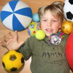 Ein Junge, der es liebt mit unterschiedlichen Bällen zu spielen.