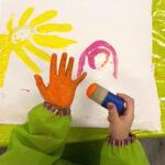 Ein Kind malt mit einem Schwamm und den eigenen Händen.